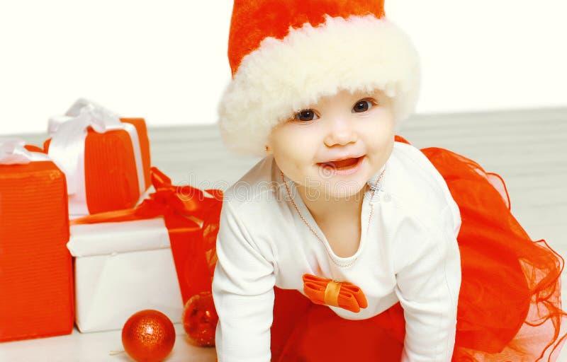 Weihnachts- und Leutekonzept - nettes lächelndes Kind in rotem Hut Sankt mit Kastengeschenken stockfotografie