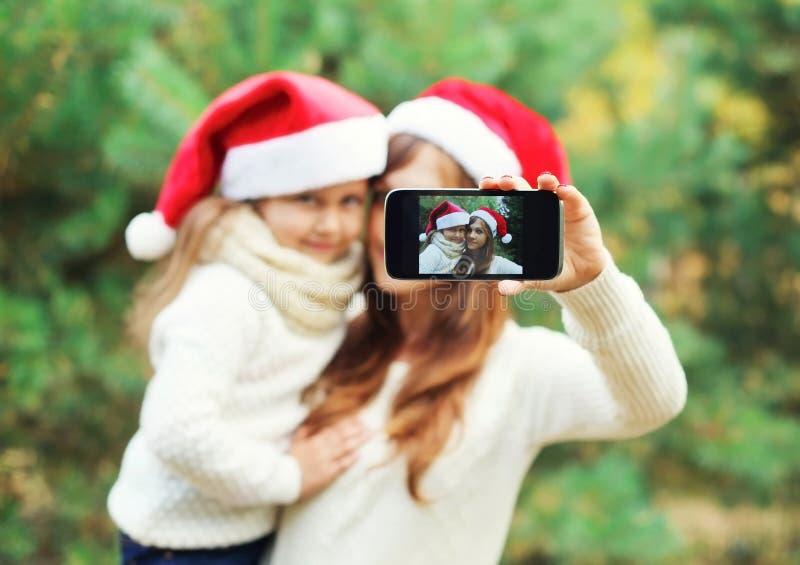 Weihnachts- und Technologiekonzept - Mutter und Kind, die zusammen Bildselbstporträt auf Smartphone nehmen stockbild