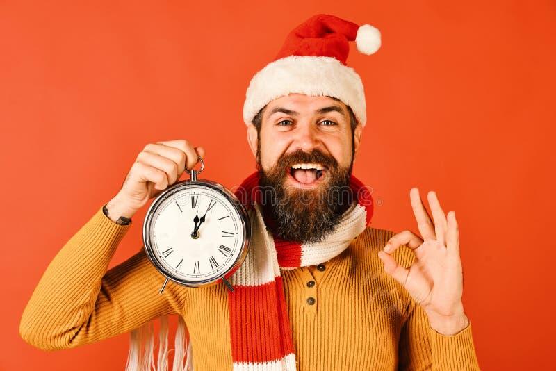 Weihnachtsabend und Zeit, Konzept zu feiern Sankt hält Uhr stockbilder