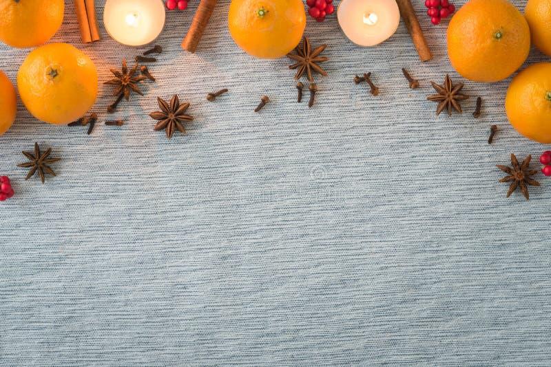 Weihnachtsanordnung für Feiertagsgewürze, -orangen und -kerzen stockfotografie