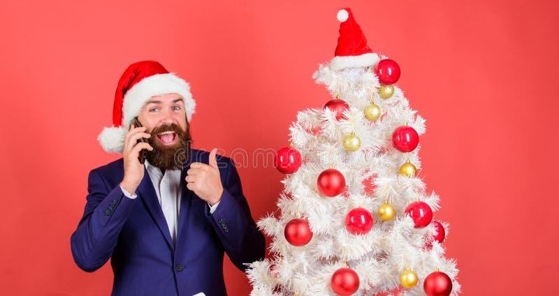 Weihnachtsanruf Create santa nennt diese Weihnachtszeit Kleideranzug und Santa-Hut-Handy Manager gratuliert lizenzfreie stockfotografie