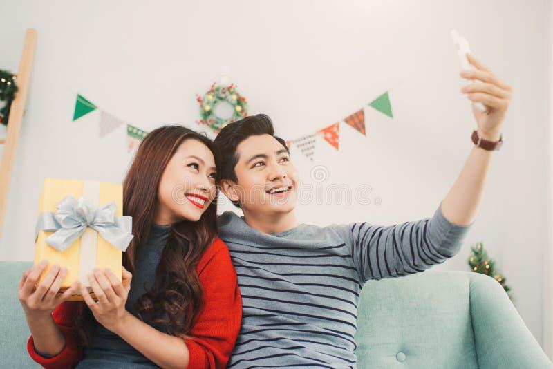 Weihnachtsasiats-Paare Ein gutaussehender Mann, der ihre Freundin/wif gibt stockbilder