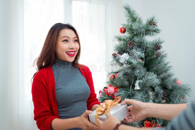 Weihnachtsasiats-Paare Ein gutaussehender Mann, der ihre Freundin/wif gibt lizenzfreies stockbild