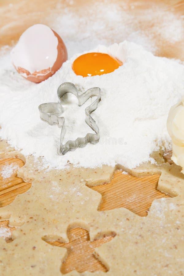 Weihnachtsbäckerei: Schneeengelsschneider im Mehl mit Eigelb stockfotos