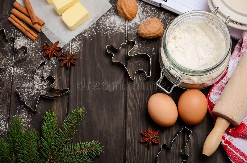 Weihnachtsbäckereibestandteile - Plätzchenschneider, -gewürze, -butter, -eier und -mehl auf dunklem hölzernem Hintergrund lizenzfreies stockfoto