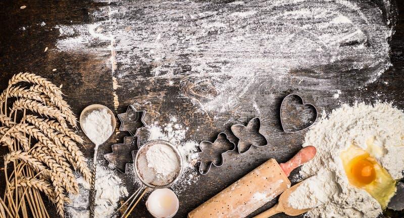 Weihnachtsbäckereihintergrund mit backen Bestandteile, Plätzchenschneider, Ohren, Ei, Mehl und Nudelholz auf rustikaler hölzerner stockfotografie