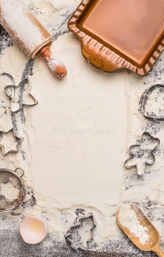 Weihnachtsbäckereihintergrund mit Mehl, Nudelholz, Plätzchenschneider und rustikale backen Wanne, Draufsicht, Platz für Text stockfotografie
