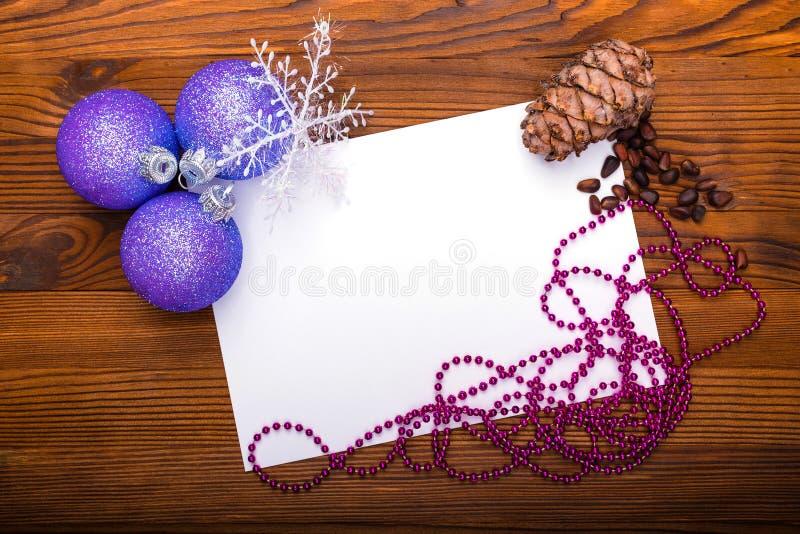 Weihnachtsbälle, Kiefernkegel und Nüsse auf einem alten hölzernen Hintergrund mit Raum für Text lizenzfreie stockfotos