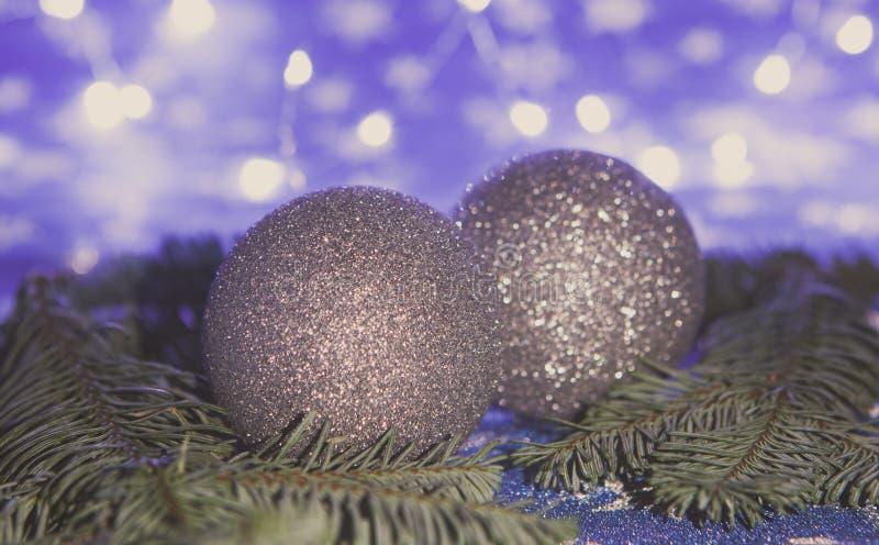 Weihnachtsbälle und -Tannenzweige auf blauem Hintergrund, Nachtbeleuchtungskonzept, getonter Hintergrund lizenzfreie stockfotografie