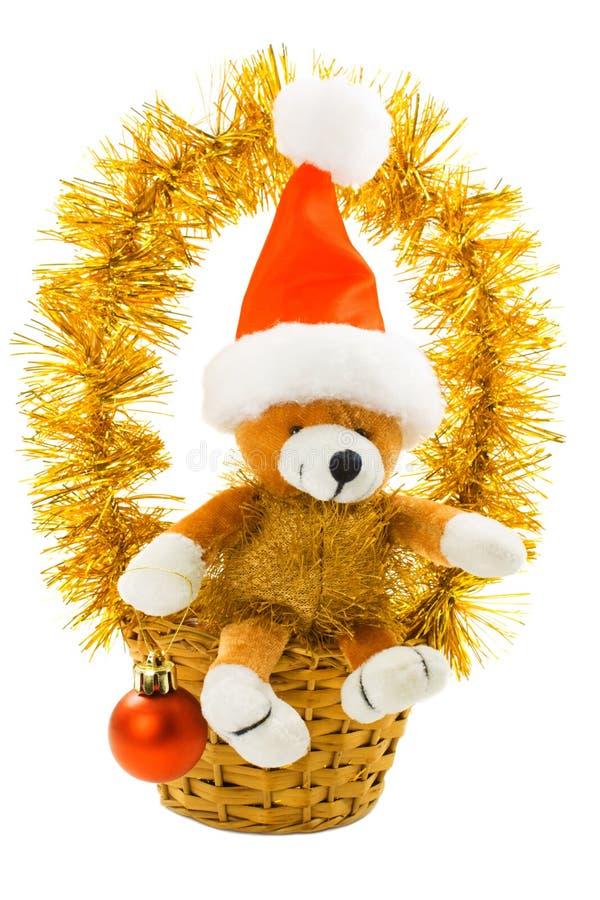 Weihnachtsbär mit Sankt-Hut und Geschenk trennte stockbild
