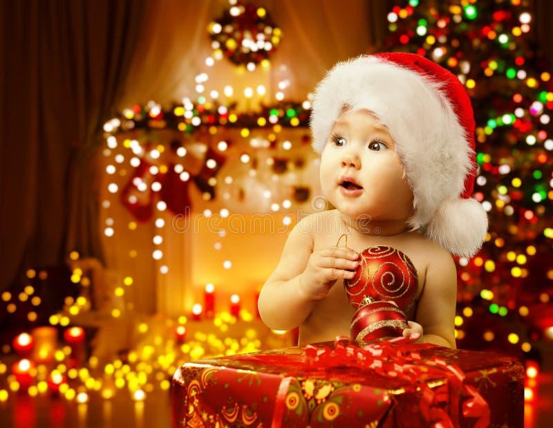 Weihnachtsbaby, das anwesendes, glückliches Kind Santa Hat, Weihnachtsgeschenk öffnet lizenzfreie stockfotos