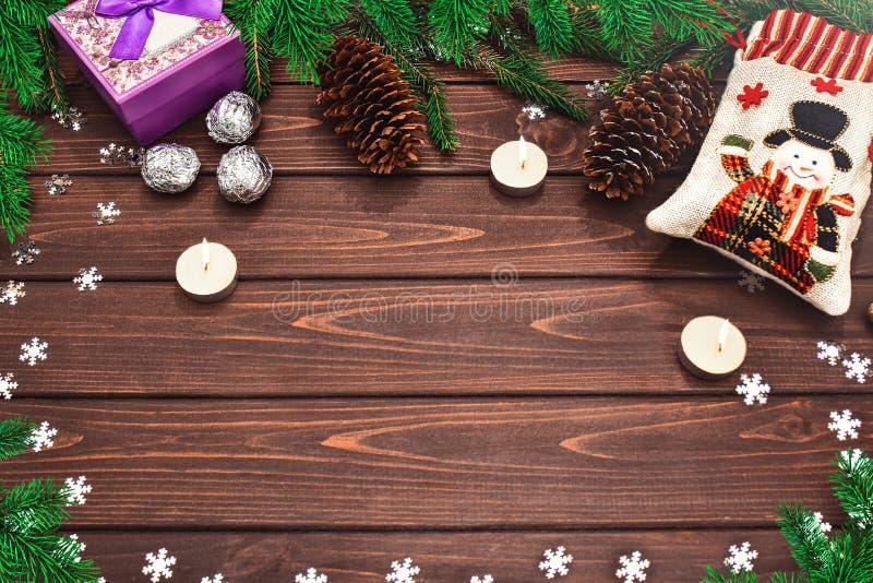 Weihnachtsbacken Zweige, Zapfen, Kerzen, Süßigkeiten und Geschenke auf einem Holztisch Textbereich Ansicht von oben Weihnachten stockfotografie