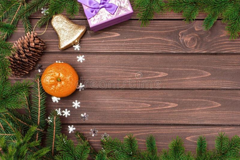 Weihnachtsbacken Zweige, Zapfen , Orange, Glocke und Geschenke auf einem Holztisch Textbereich Ansicht von oben Weihnachten stockbild