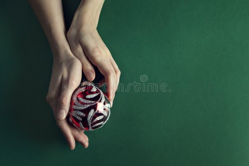 Weihnachtsball holded in den Händen einer Schönheit lizenzfreies stockbild