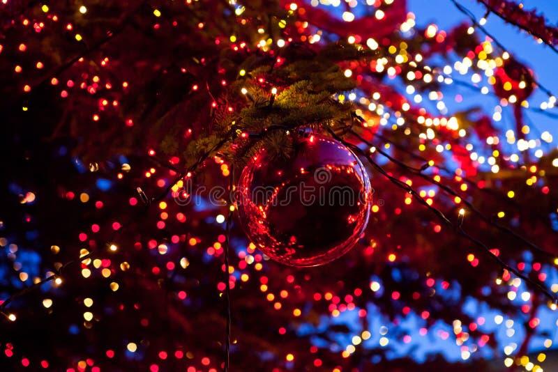 Weihnachtsball mit Verzierung beleuchtet auf einem Baum lizenzfreies stockbild