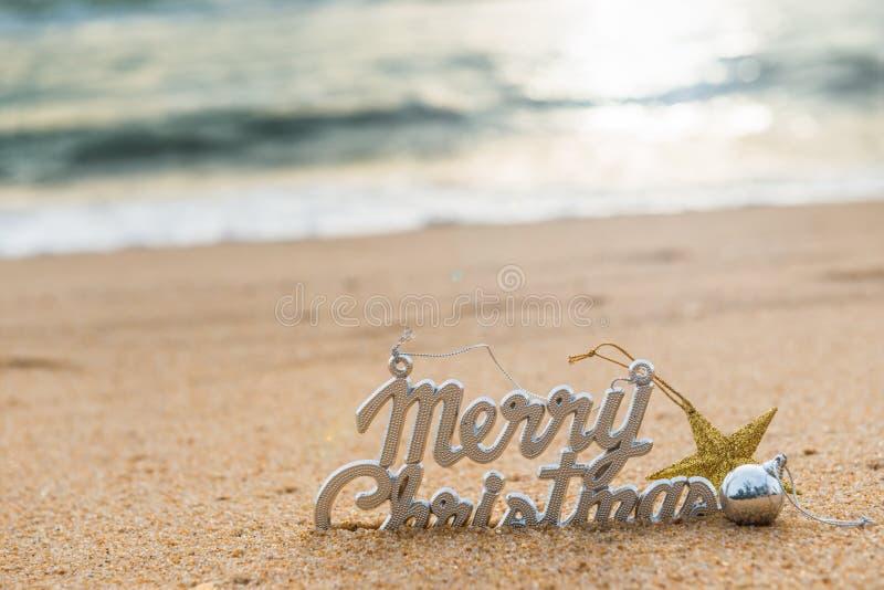 Weihnachtsballdekorationen auf dem Sand von tropischem Ozean setzen auf den Strand stockbild