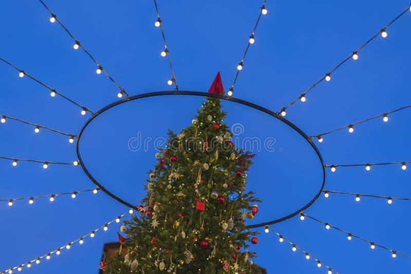 Weihnachtsbaum auf der Straße in den Lichtern und in den Girlanden gegen den Himmel stockfotos
