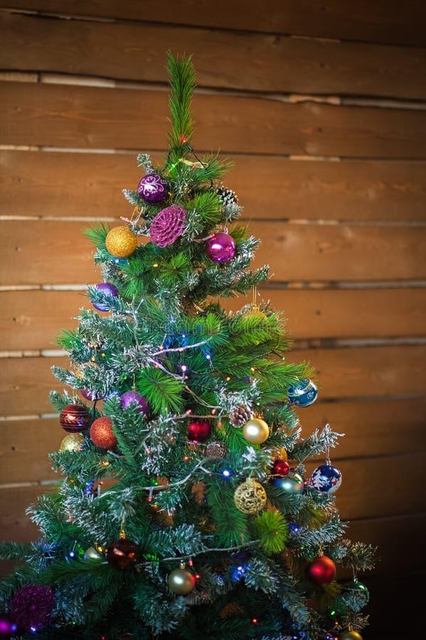 Weihnachtsbaum durch den Kamin Skandinavischer Schlafzimmerinnenraum unter Weihnachten Rustikales strukturiertes hölzernes Bett stockfoto