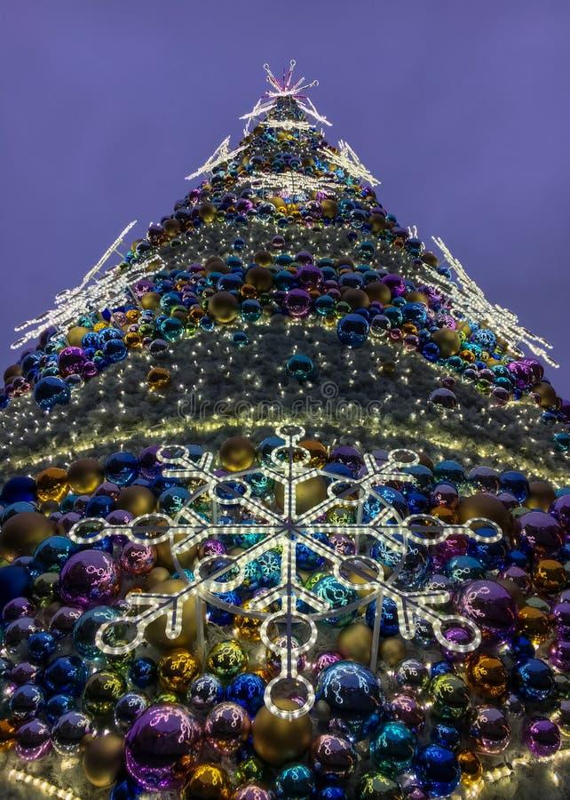 Weihnachtsbaum gemacht von den bunten Glaskugeln mit riesigen hellen glänzenden Schneeflocken lizenzfreie stockbilder