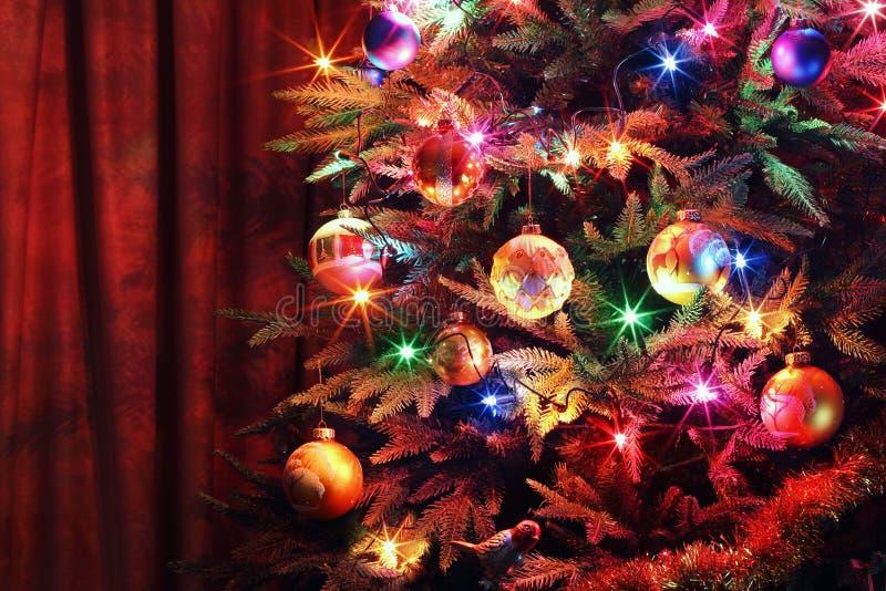 Weihnachtsbaum mit Bällen, glühender Girlande und Lametta stockbild