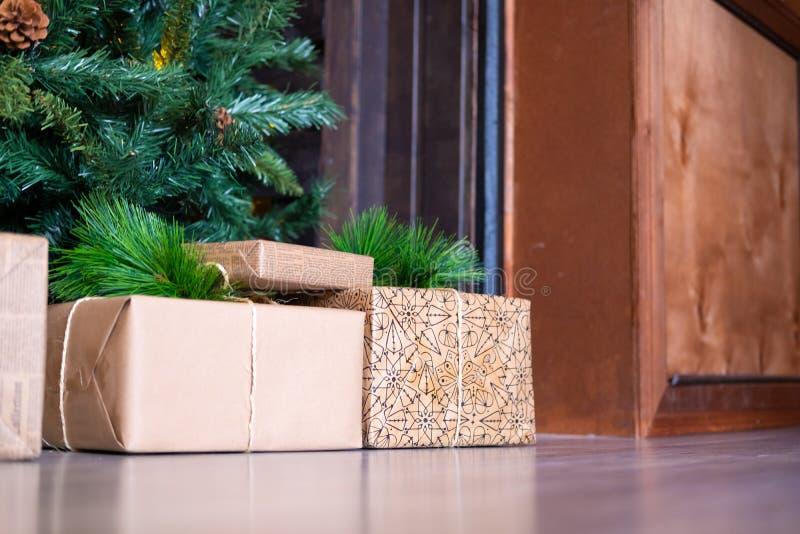 Weihnachtsbaum mit hölzernen rustikalen Dekorationen und Geschenken unter ihm im Dachbodeninnenraum stockfoto