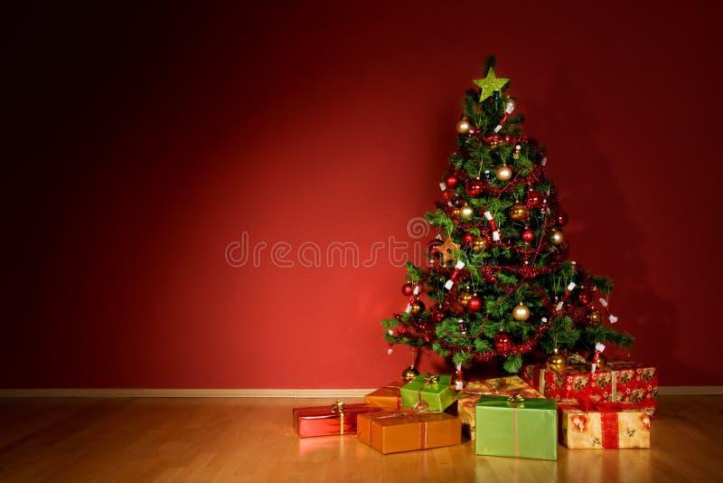 Weihnachtsbaum mit Weihnachtsgeschenken im roten Raum stockbilder