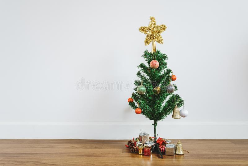 Weihnachtsbaum mit Weihnachtsgeschenken und Dekorationen auf Bretterboden, im Wohnzimmer lizenzfreie stockbilder