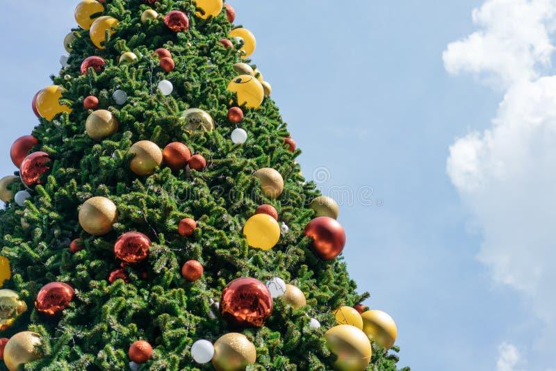 Weihnachtsbaum verziert mit den roten, gelben und silbernen Verzierungen mit hellem Himmelhintergrund Für Fahne mit Kopienraum stockbilder