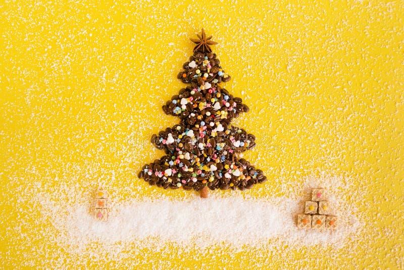 Weihnachtsbaum von den Kaffeebohnen und von den Weihnachtsgeschenken von den Waffeln verzierte Kokosnusschips auf einem gelben Hi stockfoto