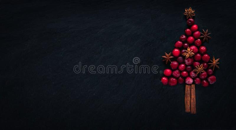 Weihnachtsbaum von gefrorenen Kirschen, Zimtstangen und Sternanis, auf dunklem backround Weihnachtsniederlassung und -glocken lizenzfreies stockfoto