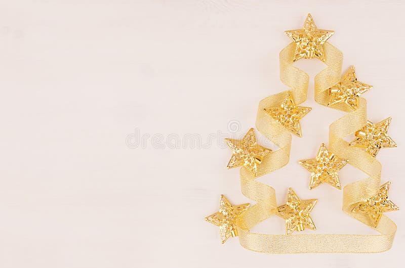 Weihnachtsbaum von Goldsternen, Lockenbänder auf weichem weißem hölzernem Brett stockbild