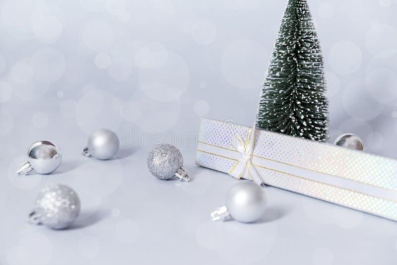 Weihnachtsbaum, Weihnachtsbälle, Geschenkbox auf einem grauen Hintergrund, neues Jahr, Stillleben stockfotos
