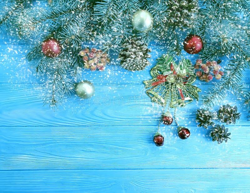 Weihnachtsbaumast auf Jahreszeit ein blauer hölzerner dekorativer Hintergrund, Schnee, Rahmen, Kiefernkegel lizenzfreie stockfotos