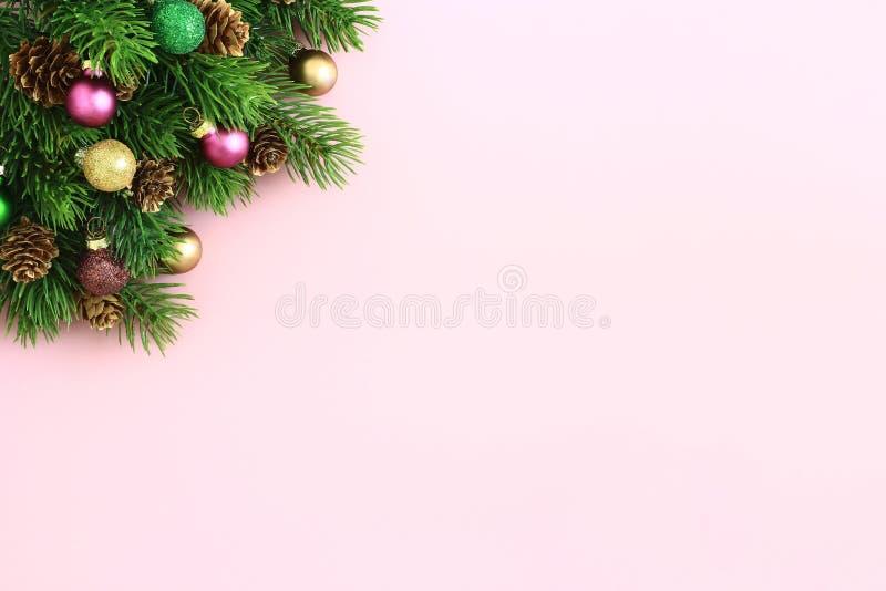 Weihnachtsbaumaste, -kegel und -bälle auf Pastellrosahintergrund lizenzfreies stockfoto