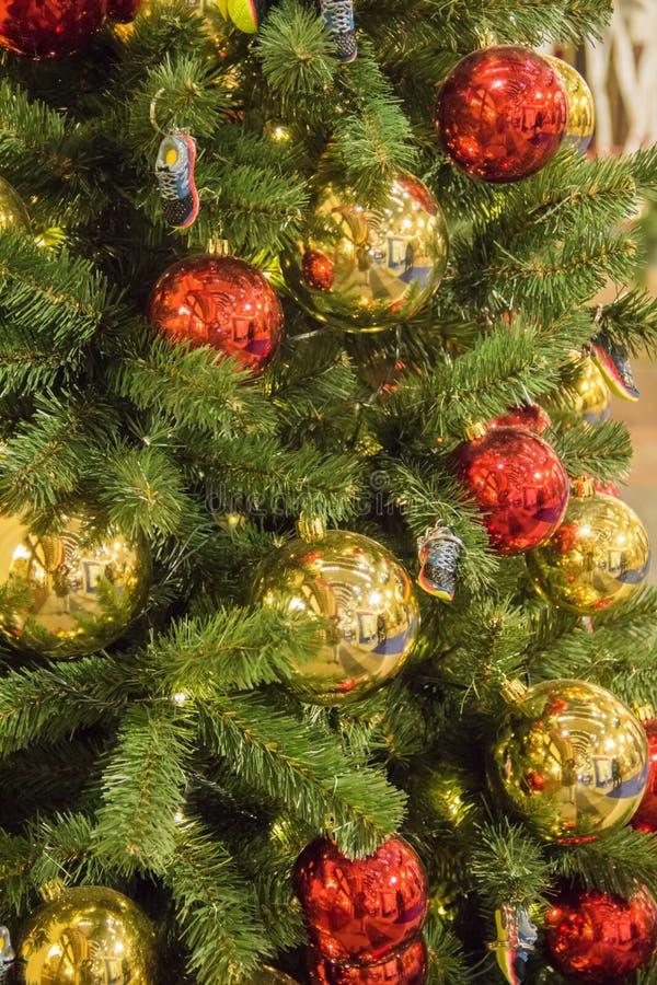 Weihnachtsbaumhintergrund und Weihnachtsdekorationen Bunte Bälle und Turnschuhspielwaren auf grüner Tanne Guten Rutsch ins Neue J lizenzfreies stockfoto