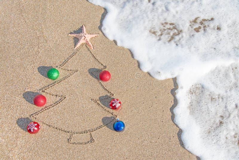 Weihnachtsbaumkontur mit Dekorationen, Stern und Welle auf dem Strand stockbilder