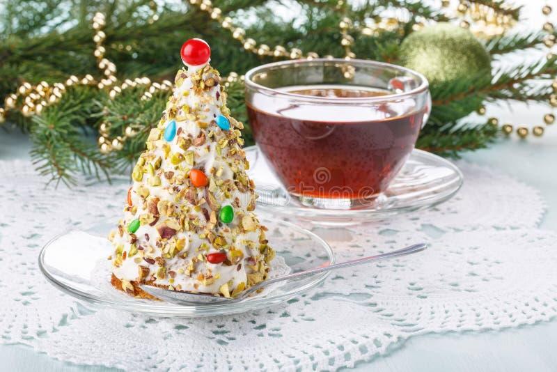 Weihnachtsbaumkuchen in der festlichen Dekoration Kleiner Kuchen in der Form des Weihnachtsbaums mit Tasse Tee stockbild