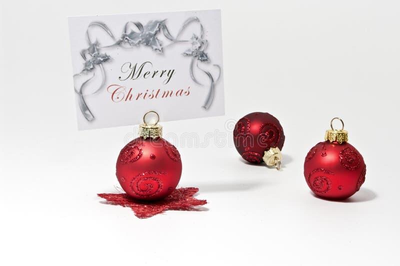Weihnachtsbaumkugeln und Grußkarte stockbild