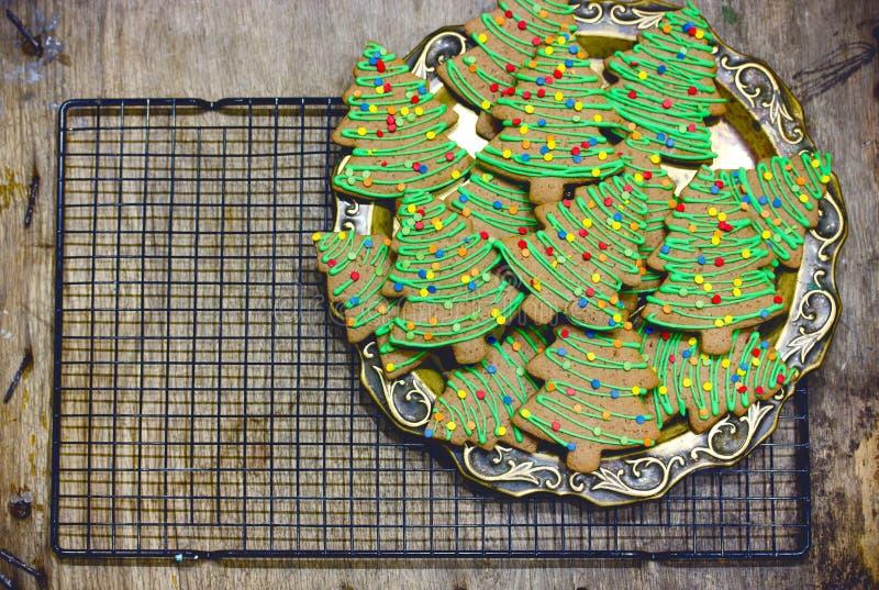 Weihnachtsbaumplätzchen - selbst gemachte Lebkuchenplätzchen mit grüner Zuckerglasur und buntem Zucker besprüht stockfotografie