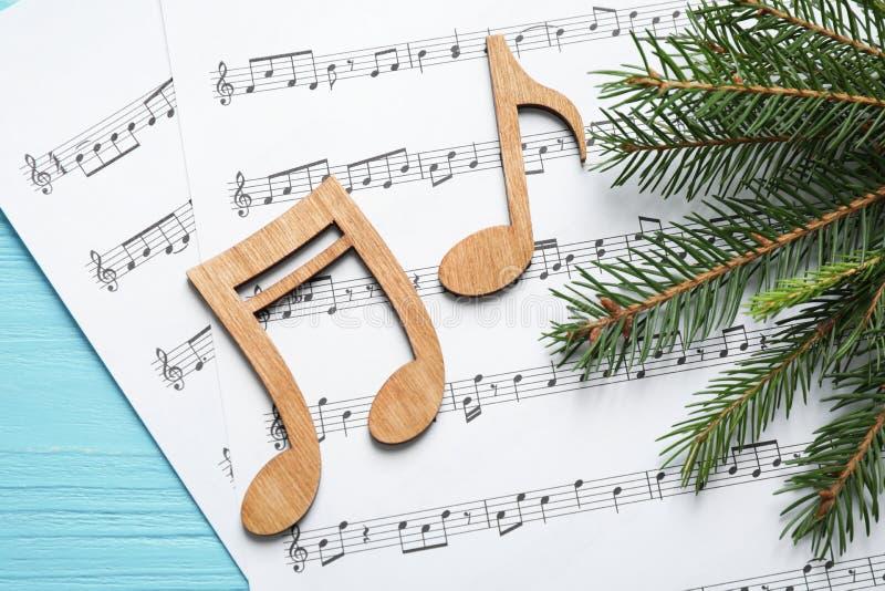 Weihnachtsbaumzweig, Noten und Musikblätter auf Holztisch, flach gelegt lizenzfreies stockbild