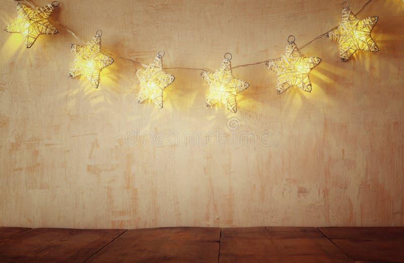 Weihnachtsbeleuchtet warme Goldgirlande auf hölzernem rustikalem Hintergrund stockbild