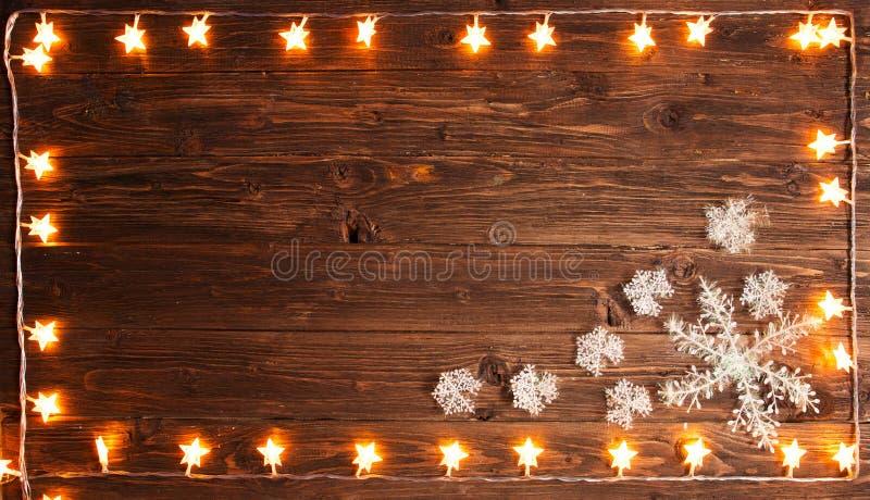 Weihnachtsbeleuchtet warme Goldgirlande mit Schneeflocken auf hölzernem rustikalem Hintergrund Weihnachts- oder des neuen Jahresk stockfotografie