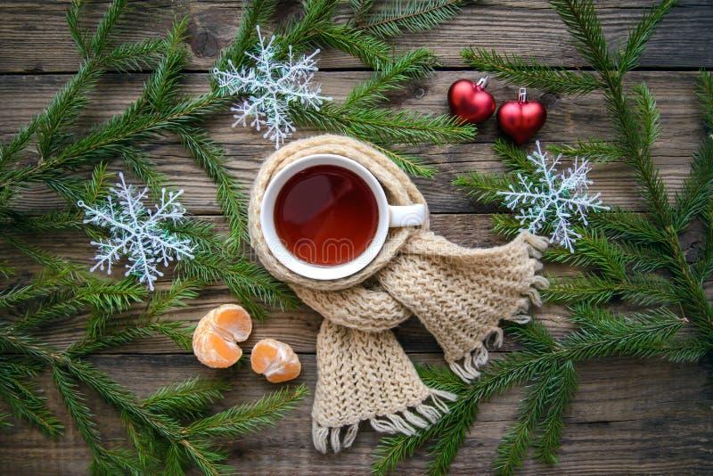 Weihnachtsbild mit einem Becher Tee in einem Schal stockfoto