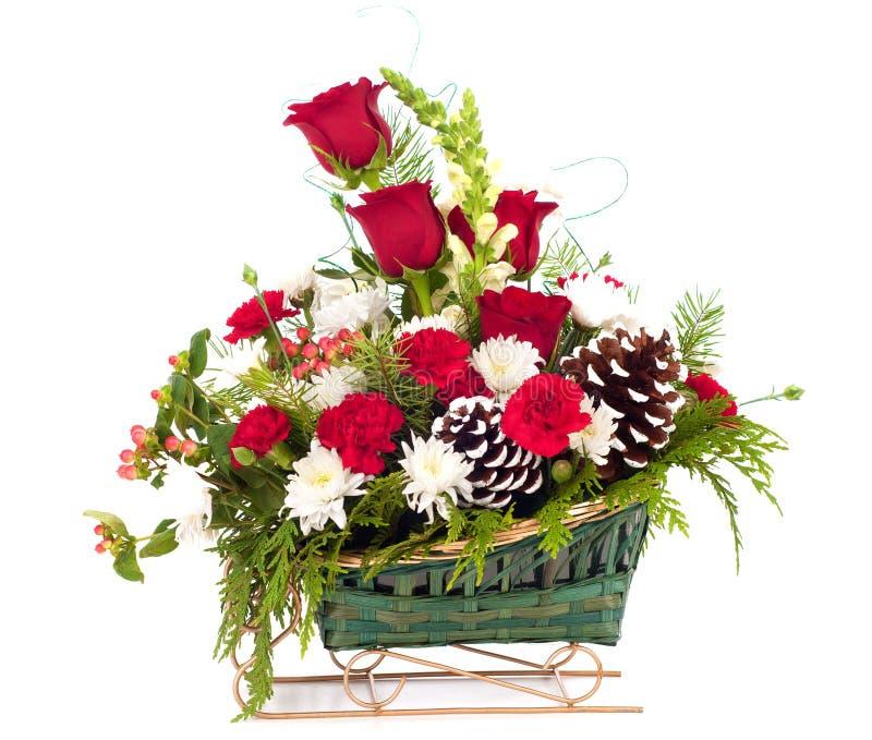 Weihnachtsblumenstrauß von Blumen im Pferdeschlitten-Korb stockfotografie
