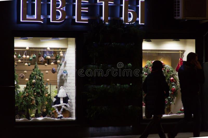 Weihnachtsdekoration auf einem Shopfenster Weihnachtsmann-Puppe, Weihnachtsbaum, Socke, Feiertagskranz Wort ` blüht ` auf russisc stockfotos