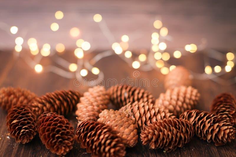 Weihnachtsdekoration in den braunen Farben Schließen Sie herauf Dekorstöße des neuen Jahres und bokeh Girlande auf hölzernem Hint lizenzfreies stockbild