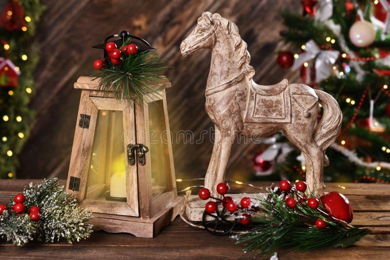 Weihnachtsdekoration mit hölzernem Pferd und Retro- Kerzenlaterne stockfoto
