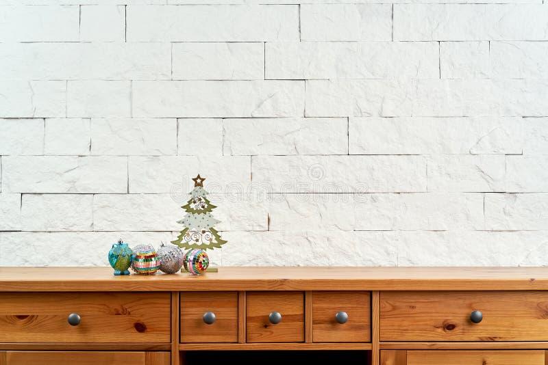 Weihnachtsdekoration mit schönem buntem Flitter im Regal auf dem Hintergrund einer Backsteinmauer lizenzfreies stockfoto