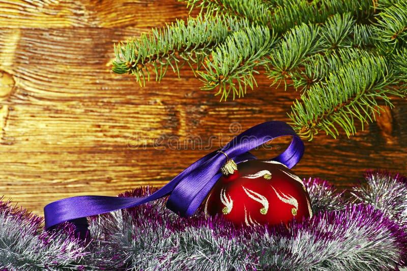 Weihnachtsdekoration. Roter Ball mit violettem Band, Tannenbaum lizenzfreie stockfotos