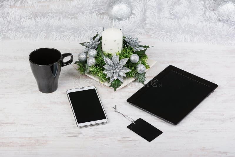 Weihnachtsdekoration, schwarzer Becher und Technologiegeräte mit leeren Bildschirmen auf weißem hölzernem Hintergrund Modell stockfotos